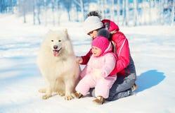 La madre y el bebé con el samoyedo blanco persiguen juntos en nieve en invierno Fotos de archivo