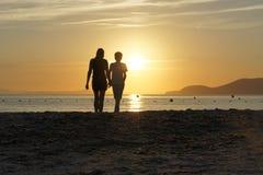 La madre y el hijo admiran juntos la puesta del sol en el mar Día de fiesta en la playa Imágenes de archivo libres de regalías