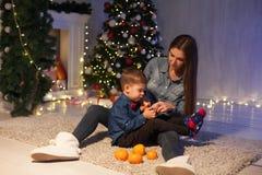 La madre y el hijo celebran el Año Nuevo en un árbol de navidad con la guirnalda de las luces de los presentes imagen de archivo
