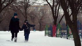 La madre y el hijo de HD están corriendo juntas llevar a cabo sus manos en el parque del invierno almacen de video