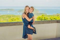 La madre y el hijo en el fondo de la playa tropical ajardinan panorama El océano hermoso de la turquesa renuncia con los barcos y foto de archivo