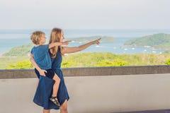 La madre y el hijo en el fondo de la playa tropical ajardinan panorama El océano hermoso de la turquesa renuncia con los barcos y fotos de archivo libres de regalías