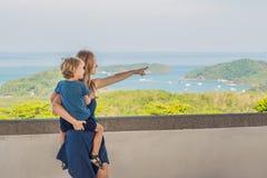 La madre y el hijo en el fondo de la playa tropical ajardinan panorama El océano hermoso de la turquesa renuncia con los barcos y fotografía de archivo