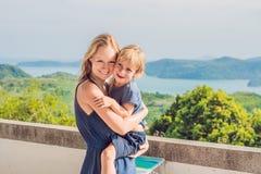 La madre y el hijo en el fondo de la playa tropical ajardinan panorama El océano hermoso de la turquesa renuncia con los barcos y imagen de archivo