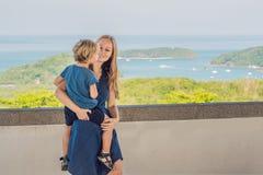 La madre y el hijo en el fondo de la playa tropical ajardinan panorama El océano hermoso de la turquesa renuncia con los barcos y imagenes de archivo
