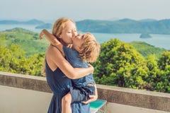 La madre y el hijo en el fondo de la playa tropical ajardinan panorama El océano hermoso de la turquesa renuncia con los barcos y fotografía de archivo libre de regalías