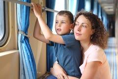 La madre y el hijo en pasillo del `s del tren mira en ventana Fotos de archivo libres de regalías