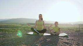 La madre y el hijo en la relajación que se sienta presentan en la parte superior de la montaña en la salida del sol por la mañana almacen de video