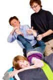 La madre y el hijo están cosquilleando al muchacho Imágenes de archivo libres de regalías