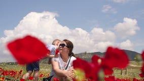 La madre y el hijo están jugando en el campo de amapolas de florecimiento almacen de video