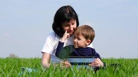 La madre y el hijo están mirando la pantalla de la tableta, sentándose en la hierba verde en el parque Experiencia de la madre y  almacen de metraje de vídeo