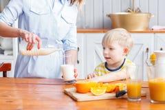 La madre y el hijo están sonriendo mientras que desayunando en cocina La mamá está vertiendo la leche en el vidrio foto de archivo