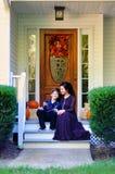 La madre y el hijo felices en el pórtico de la caída adornaron la casa Imagen de archivo libre de regalías