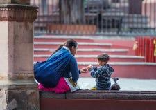 La madre y el hijo felices indígenas nativos se sientan en el vestido colorido tradicional, México, América imagen de archivo