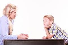 La madre y el hijo hablan y discuten se sientan en la tabla Imagen de archivo