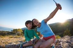 La madre y el hijo hacen el selfie encima de una montaña Fotos de archivo libres de regalías