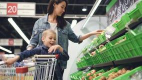 La madre y el hijo jovenes de la familia están comprando fruta en colmado, están tomando las peras y el kiwi y los están introduc almacen de video