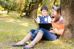 La madre y el hijo leyeron un libro juntos Foto de archivo