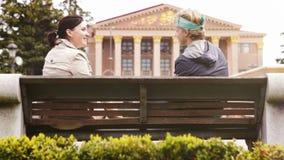La madre y el hijo que se sientan en el banco de parque de la ciudad y tienen conversación divertida metrajes
