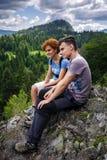 La madre y el hijo que se sientan en una montaña rematan Imagenes de archivo