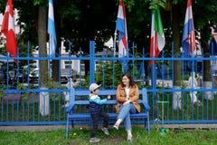 La madre y el hijo se est?n sentando en el banco fotografía de archivo libre de regalías