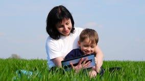 La madre y el hijo se relajan en el parque, sentándose en la hierba verde, usando una tableta Tecnología, comunicaciones y almacen de metraje de vídeo