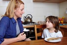 La madre y el hijo se sienta en cocina durante cena Imágenes de archivo libres de regalías