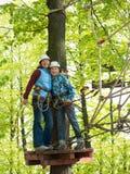 La madre y el hijo son juntos y sonríen en un casco y con una cuerda de la seguridad en el fondo del bosque Imagen de archivo libre de regalías