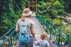 La madre y el hijo van en puente colgante El viajar con concepto de los niños Foto de archivo
