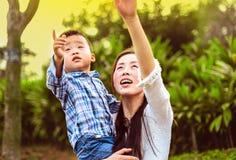 La madre y el niño chinos aumentaron sus manos para arriba y la demostración algo Caminan en el parque Imagen de archivo