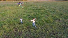 La madre y el niño corren con una cometa en un campo verde. Risas y alegría, ánimo festivo. Otoño,Amanecer metrajes