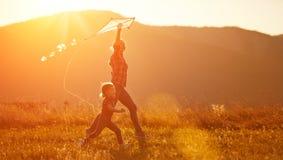 La madre y el niño felices de la familia corren en prado con una cometa en summe Fotografía de archivo