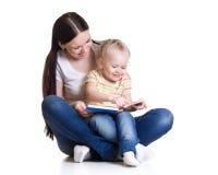 La madre y el niño felices leyeron un libro juntos Foto de archivo