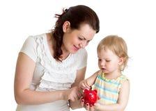 La madre y el niño felices pusieron monedas en la hucha de la hija Imagenes de archivo