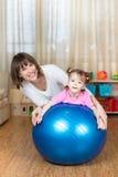 La madre y el niño juegan con la bola de la aptitud dentro Fotos de archivo libres de regalías