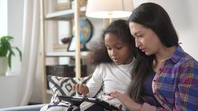 La madre y el niño moreno se está sentando en el sofá y está utilizando tecnología digital electring almacen de metraje de vídeo