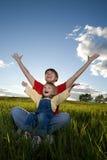 La madre y el niño se sientan en campo Fotografía de archivo libre de regalías