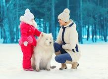 La madre y el niño con el samoyedo blanco persiguen juntos en invierno Imagen de archivo