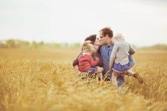 La madre y el padre celebra en las manos sus pequeños niños y se besa en un campo Foto de archivo