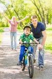 La madre y el padre enseña a su hijo a montar una bici Fotos de archivo