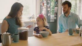 La madre y el padre jovenes están sonriendo en su hija que esté teniendo cereal para el desayuno MES lento, tiro de Steadicam almacen de video