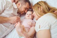 La madre y el padre juegan con el bebé en la cama imagenes de archivo