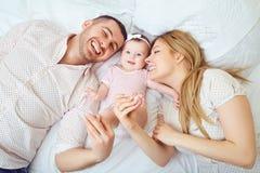 La madre y el padre juegan con el bebé en la cama imágenes de archivo libres de regalías