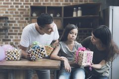 La madre y el padre sonríen en la muchacha y el intento para darle presentes, mientras que la muchacha mira tristemente a un lado Imágenes de archivo libres de regalías
