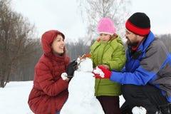 La madre y el papá con la hija sculpt el muñeco de nieve Fotos de archivo