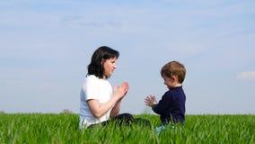 La madre y el pequeño niño se sientan en la hierba verde y el juego, dando una palmada a las manos de cada uno El concepto de fam metrajes