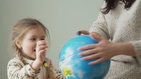 La madre y la hija adorable hace girar el globo y estudia la geografía en forma del juego almacen de metraje de vídeo