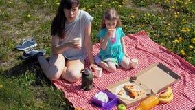 La madre y la hija comen la pizza por el mar de la costa metrajes