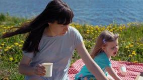 La madre y la hija comen la pizza por el mar de la costa almacen de metraje de vídeo