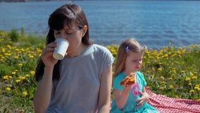 La madre y la hija comen la pizza por el mar de la costa almacen de video